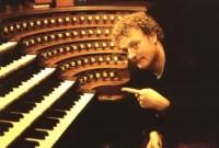 Howard pointing at the keyboard of an organ