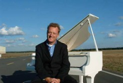 Howard Goodall at a white grand piano
